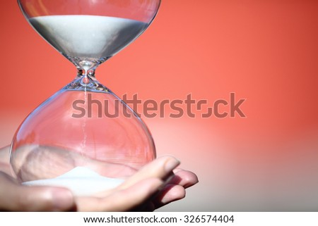 Hand holding a modern hourglass -- sand trickling through the bulbs of a crystal sand glass. symbol of time. countdown. Time Management. Hourglass timer concept for business deadline and leadership - stock photo