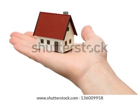 Hand holding a new house. Isolated over white background
