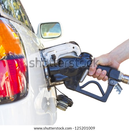 Hand holding a nozzle while fueling white car.  Focus on the nozzle.