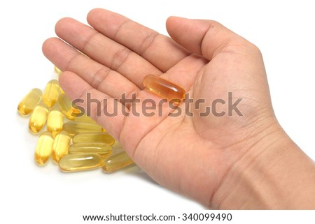 Hand holding a omega 3 gel Fish oil capsules with white blurred background - stock photo