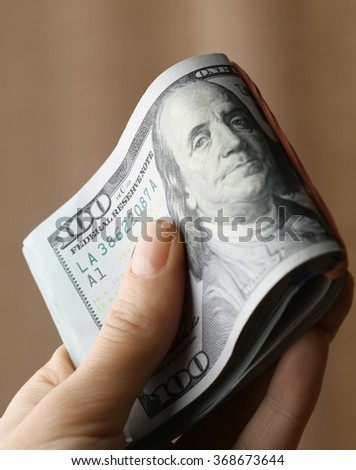 Hand holding a pack of dollars on blurred background