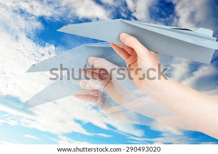 Hand holding a paper airplane against cloudy sky - stock photo