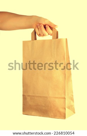 Hand holding a paper bag. Toned image - stock photo