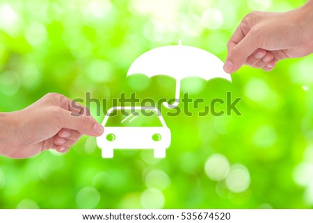 Hand holding a paper car and umbrella on green background
