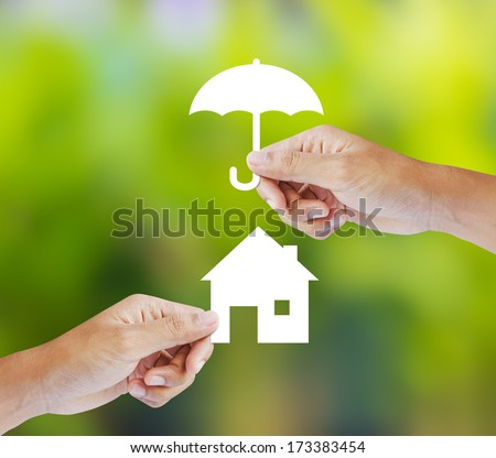 Hand holding a paper home and umbrella on green background - stock photo