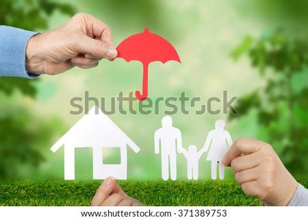 Hand holding a paper home, umbrella and  family on green background, protection concept