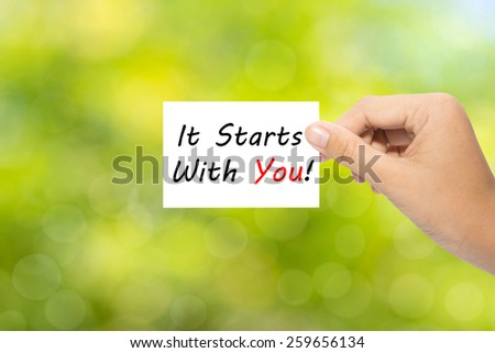 Hand holding a paper It Starts With You! on green background  - stock photo