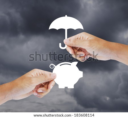 Hand holding a paper  piggy bank and umbrella, Insurance concept - stock photo