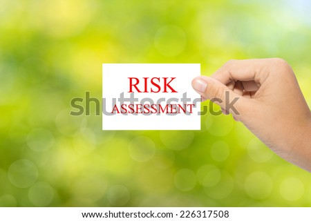 Hand holding a paper RISK ASSESSMENT on green background  - stock photo