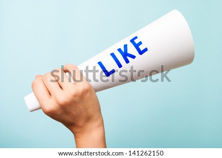 """Hand holding a paper white megaphone with the word """"LIKE"""", on blue background. Social media and internet concept. - stock photo"""