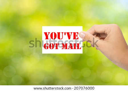 Hand holding a paper YOU'VE GOT MAIL on green background - stock photo