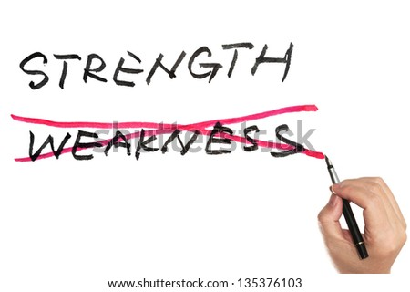 Hand holding a pen and choosing between strength and weakness