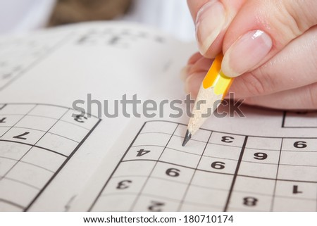Hand Holding a Pen Playing Sudoku - stock photo