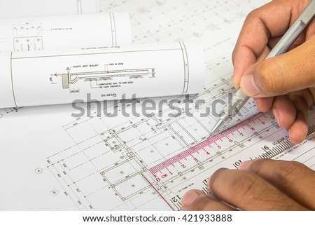 Hand holding a pencil, ruler engineer writing on the Blue Print a blueprint. Place the rolls on a desk over blurred blueprint. - stock photo