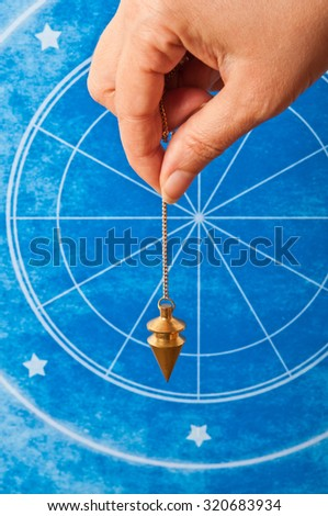 hand holding a pendulum against an astrological background - stock photo