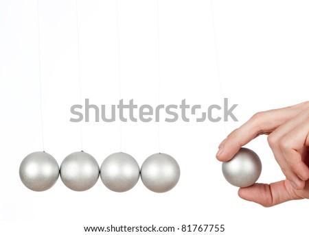 hand holding a pendulum ball - stock photo