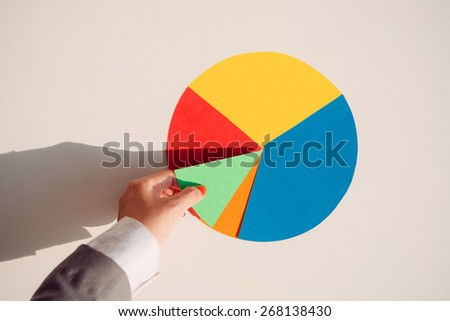Hand holding a piece of colorful paper circular diagram