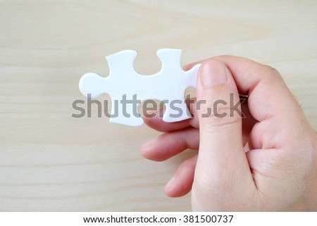 Hand holding a piece of jigsaw puzzle, background, template, business concept