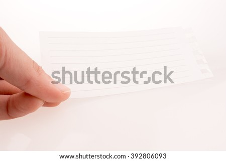 Hand holding a piece of lined paper on a white background