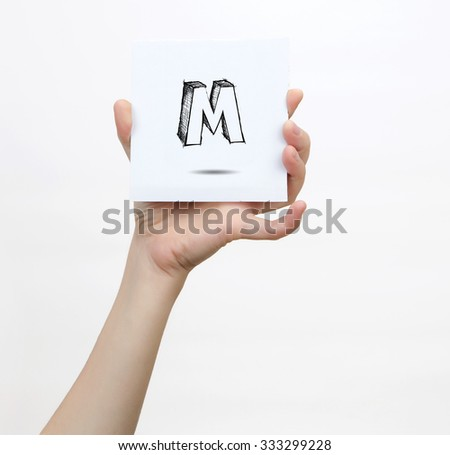 Hand holding a piece of paper with sketchy capital letter M, isolated on white. - stock photo