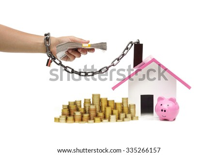 hand holding a pile of banknote and chained with a house - burden and debts of buying a new house concept