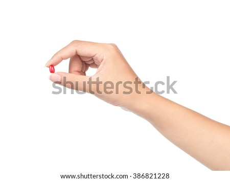 Hand holding a pill between thumb and forefinger isolated on white background