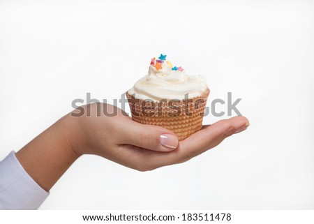 hand holding a pink cupcake decorated with hearts on white - stock photo