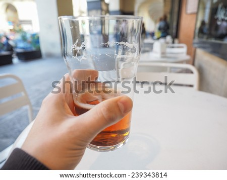 Hand holding a pint of British ale on a pub table - selective focus on beer over blurred background - stock photo