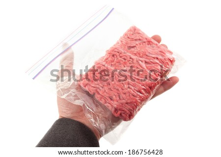 Hand holding a portion of beef ground beef in plastic bag - stock photo