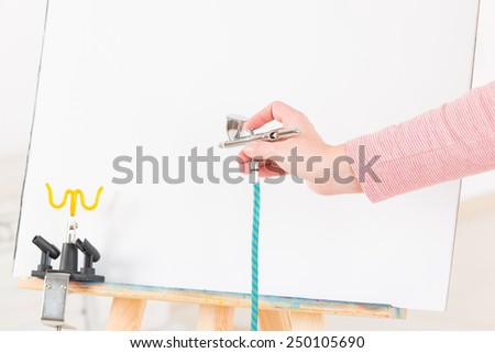 Hand holding a professional airbrush over white canvas or background - stock photo