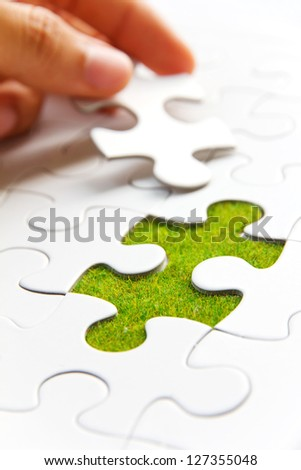hand holding a puzzle piece, green space concept - stock photo