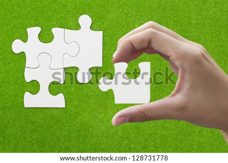 hand holding a puzzle piece on green background - stock photo