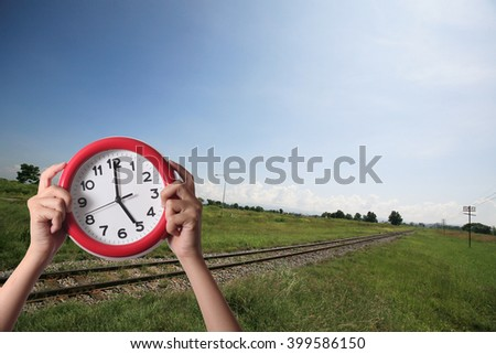 hand holding a red clock on the rural countryside background  - stock photo
