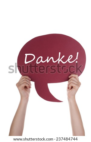 Hand Holding A Red Speech Balloon Or Speech Bubble With German Danke. Isolated Photo - stock photo