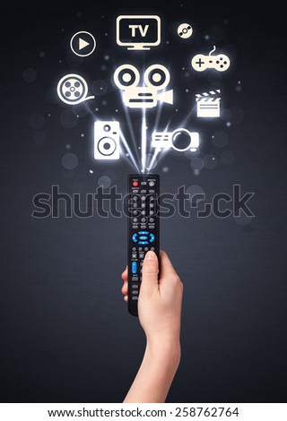 Hand holding a remote control, media icons coming out of it  - stock photo