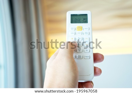 Hand holding a remote control of air conditioner - stock photo