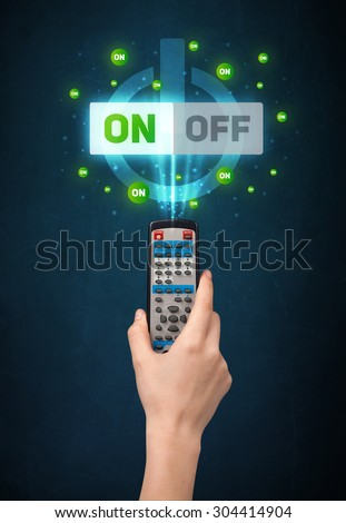 Hand holding a remote control, on-off signal coming out of it  - stock photo