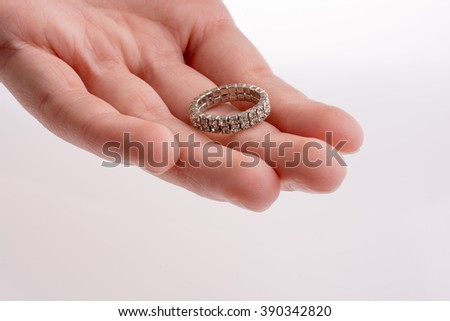 Hand holding a ring on a white background