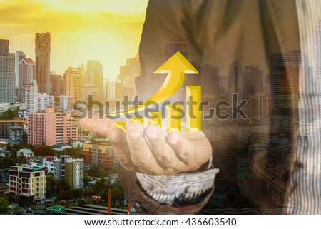 Hand holding a rising arrow/representing business growth/business concept on cityscape background  - stock photo