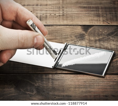 hand holding a rolled dollar bill for cocaine (drug concept) - stock photo