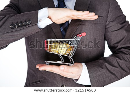 hand holding a shopping cart full of gold