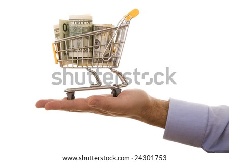 hand holding a shopping cart full of money (selective focus)