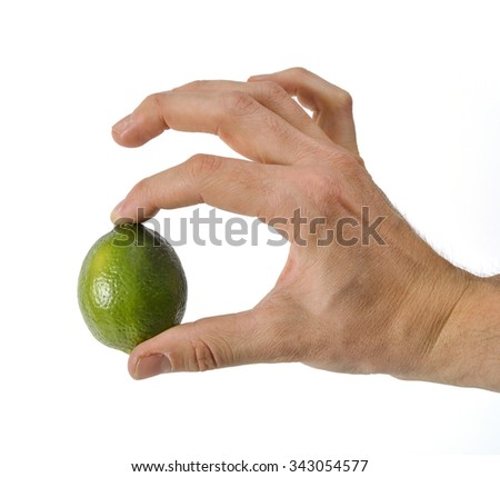 Hand holding a single lime isolated on white