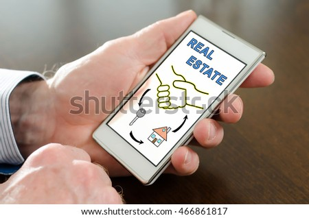 Hand holding a smartphone with real estate concept