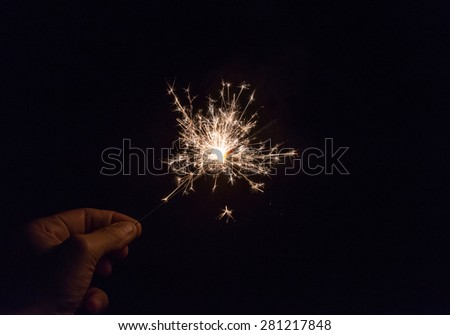 hand holding a sparkler fire on black background. - stock photo
