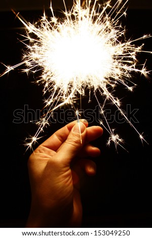 Hand holding a sparkler - symbolic image - stock photo