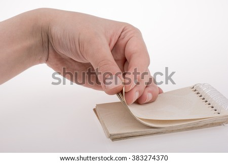 Hand holding a spiral notebook on a white background