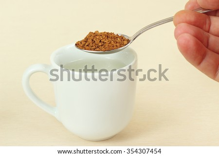Hand holding a spoon with instant coffee over the coffee cup  - stock photo