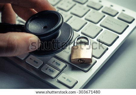 hand holding  a stethoscope over computer keyboard with a security lock - computer system check and maintenance concept - stock photo
