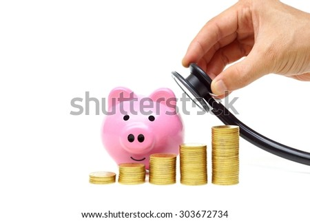 hand holding a stethoscope with piles of coins arranged as a graph and a pink piggy bank - healthcare cost concept - stock photo
